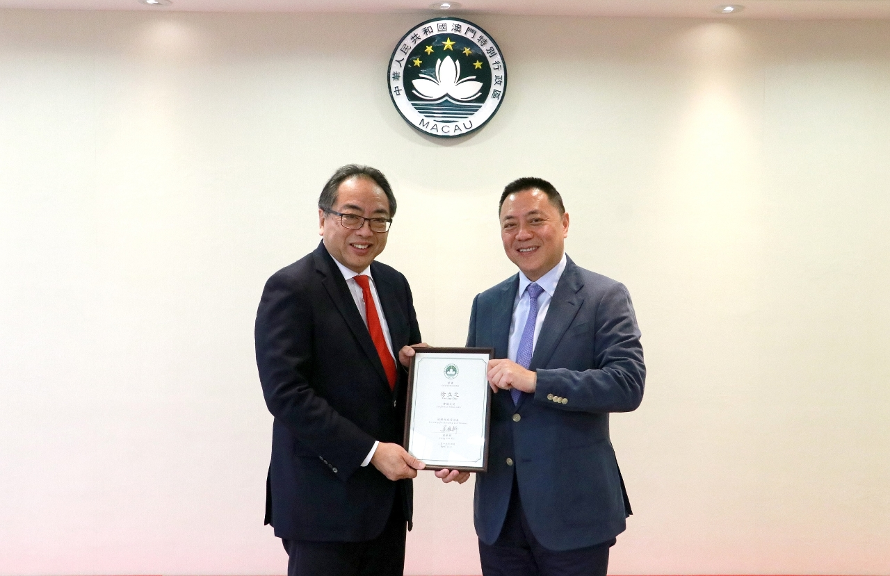 "The Secretary for Economy and Finance Mr Leong Vai Tac confers the certificate of appointment as ""Conference Ambassador"" to Prof Tsui Lap Chee, President and Founding member of the Academy of Science of Hong Kong and world-renowned molecular biologist"
